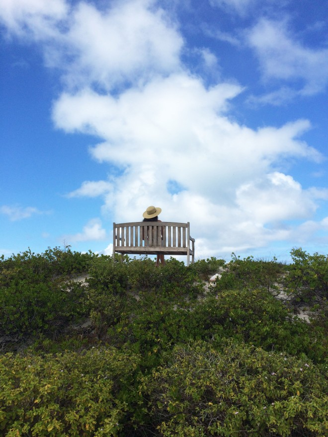 girl on bench in anegada with sky