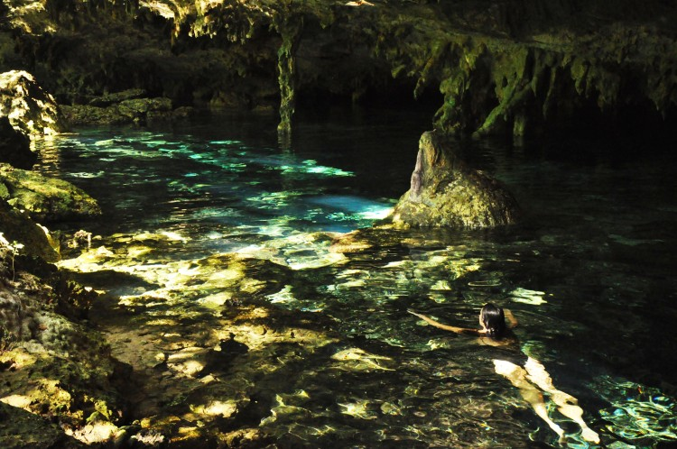 Girl swimming in dappled cenote