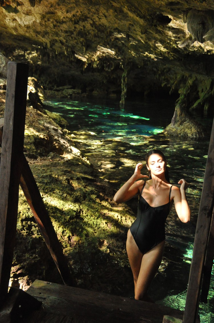 Girl coming out of cenote in swimsuit