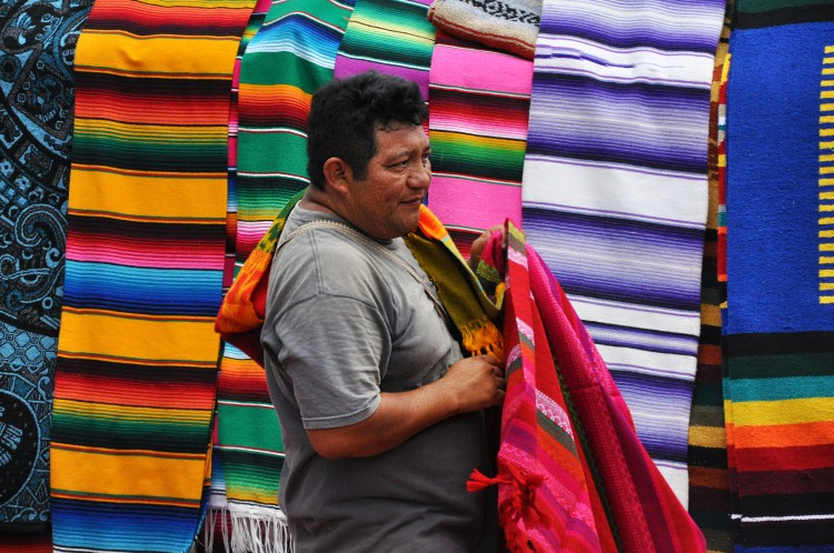 Man selling colourful hand-made rugs mexico