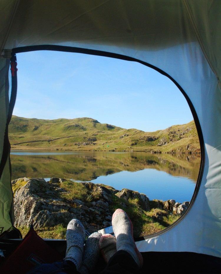 feet in tent with view of lake