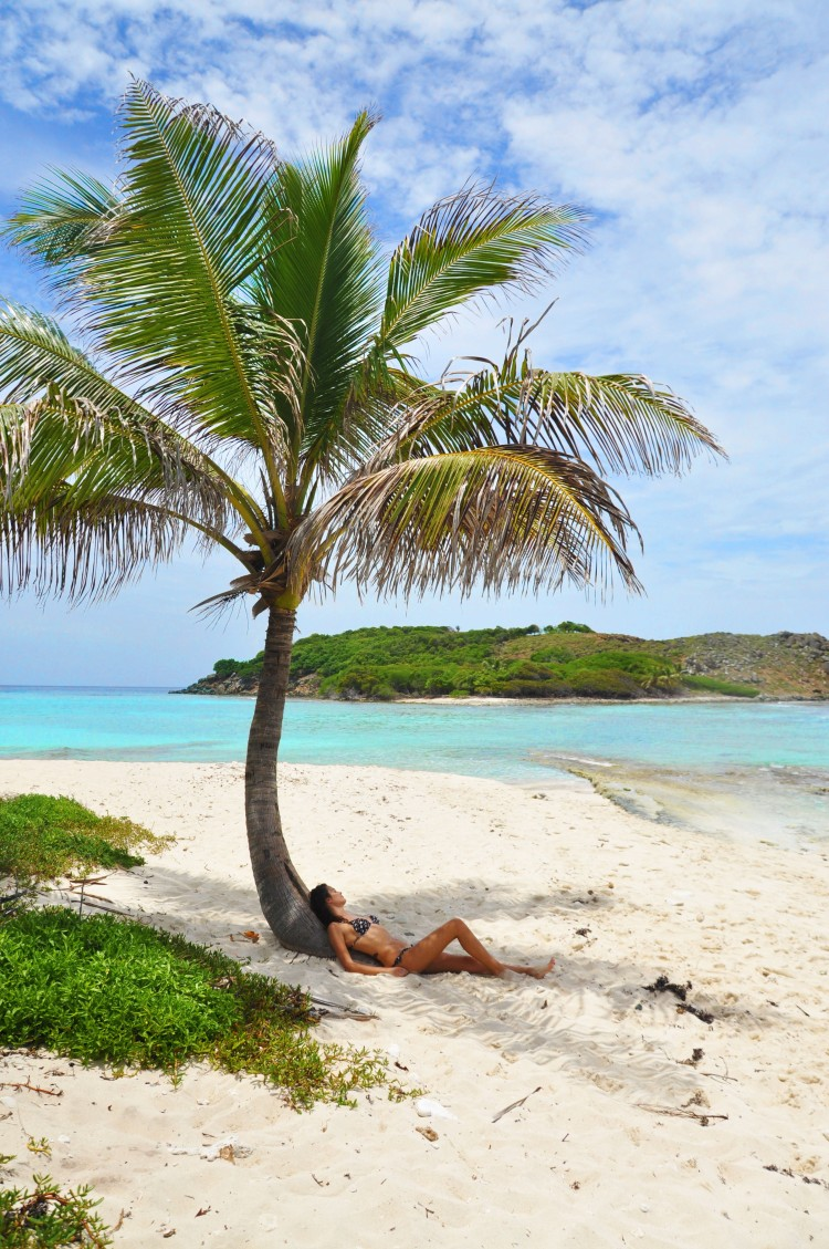 Girl under palm tree on sandy spit in BVI