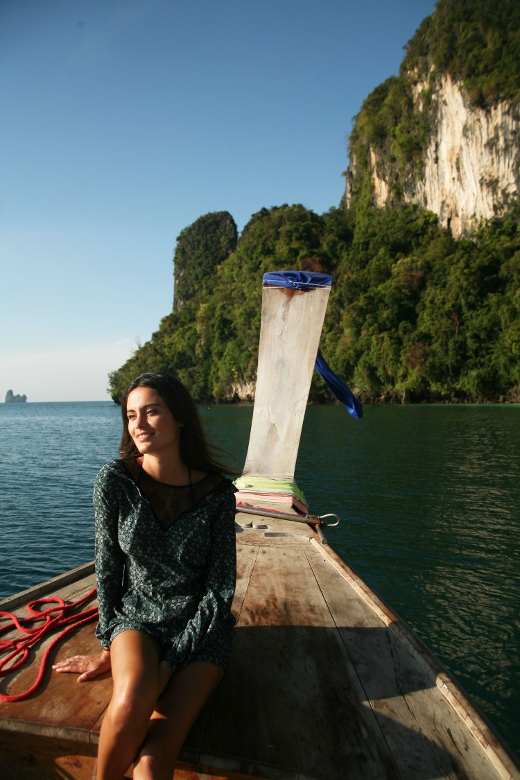 girl on longtail boat with rocks thailand