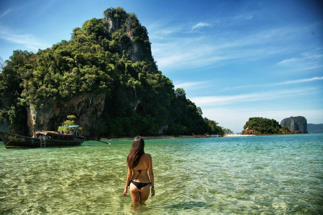 girl in water in front of rock thailand