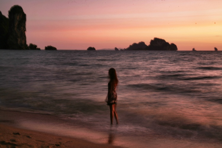 girl at sunset with rocks in thailand