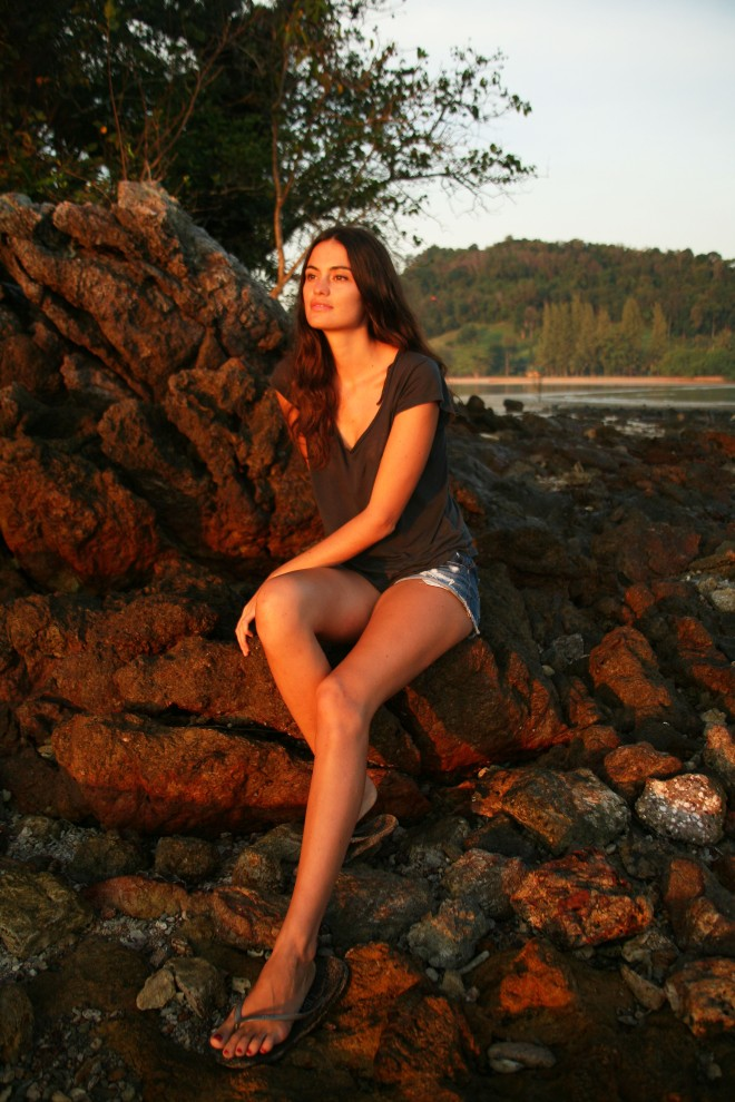 Girl on rocks with sunrise